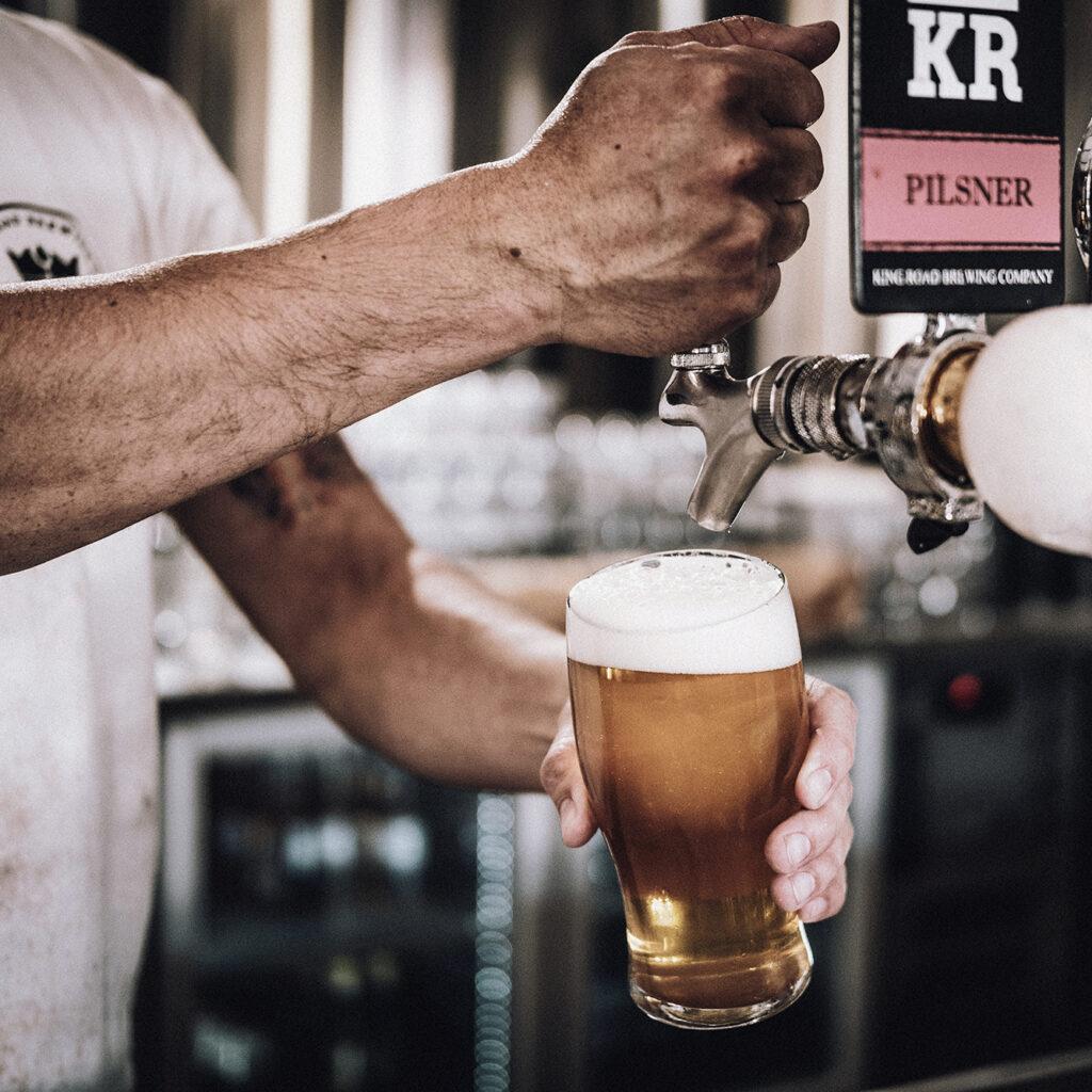 Bartender pouring King Road Pilsner on tap